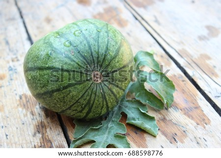 Watermelon with green leaves on wooden boards #688598776