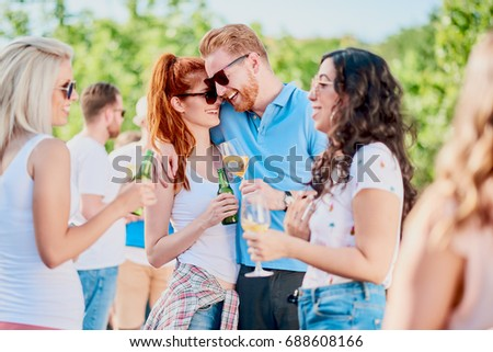 Couple hugging and flirting at outdoor party #688608166