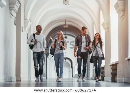 Multiracial students are walking in university hall during break and communicating. Royalty-Free Stock Photo #688627174