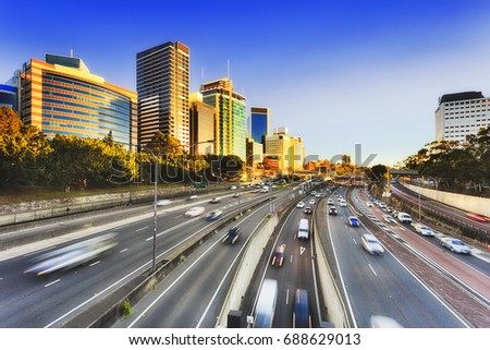 Sydney Warringah freeway going through high-rise buildings of North Sydney. Tall modern architectural office towers and serviced apartments face rising sun above multi-lane transport corridor. Royalty-Free Stock Photo #688629013