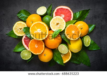 Fresh citrus fruit assortment. Different citrus fruit on black slate table. Fruit food background. Healthy eating and diet. #688635223