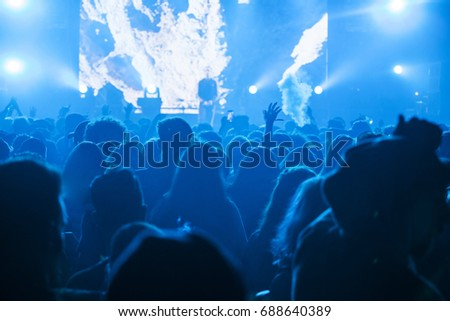 Crowd at concert - Cheering crowd in front of bright colorful stage lights #688640389