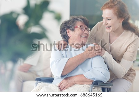 Happy patient is holding caregiver for a hand while spending time together Royalty-Free Stock Photo #688645165