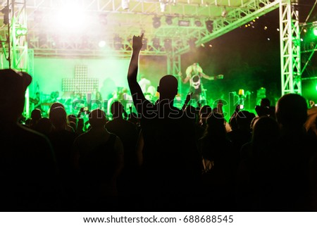ODESSA, UKRAINE August -1, 2017: fans are enjoying concert in fan zone of hall during concert of hamlet-metal band Rammstein. crowd of people silhouettes with their hands up. Selective focus #688688545