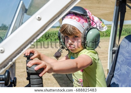 ROMA, ITALY - JULY 2017: Little charming little girl pilot, child in the cockpit of light-engine aircraft Tecnam P92-S Echo #688825483