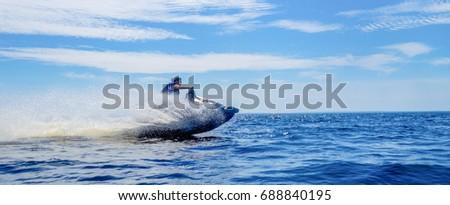 Woman speeding on jet ski on lake during summer vacation