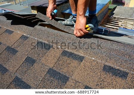 Repairing of roof by cutting felt or bitumen shingles during waterproofing works. #688917724
