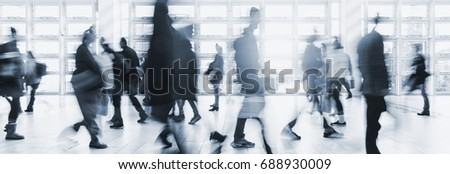blurred crowd commuting traveling walking in a modern hall #688930009