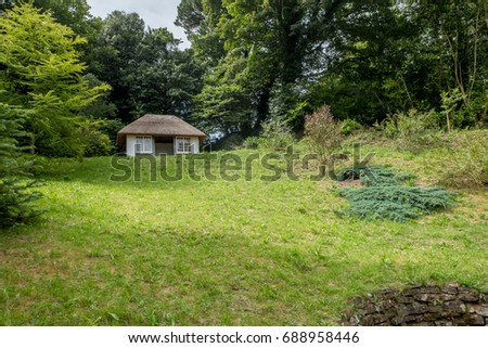 old white thatched house in the garden.  #688958446