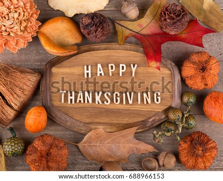 Wood plaque with Happy Thanksgiving lettering surrounded with colorful autumn decorations #688966153