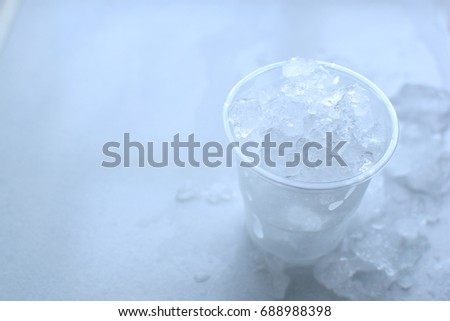 Ice in plastic glass and on white table. #688988398