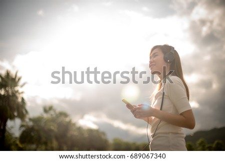Beautiful young woman listening to music in headphones and phone on park. #689067340