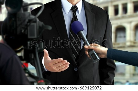 Close-up press interview with a man in black suit #689125072