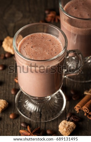 Chocolate, coffee, milk, banana shake on wooden background. Smoothie with spices cinnamon, anise, brown sugar. Milkshake and hot winter drink concept. Protein diet. Healthy food concept. #689131495