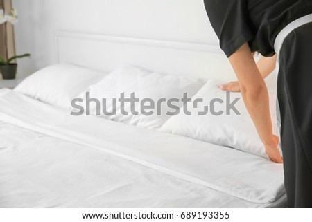 Young maid making bed in hotel room #689193355