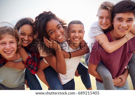 Teenage school friends having fun piggybacking outdoors Royalty-Free Stock Photo #689215405