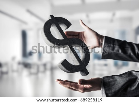 Closeup of business woman in black suit keeping stone dollar sign in hands with office view on background. Mixed media. #689258119