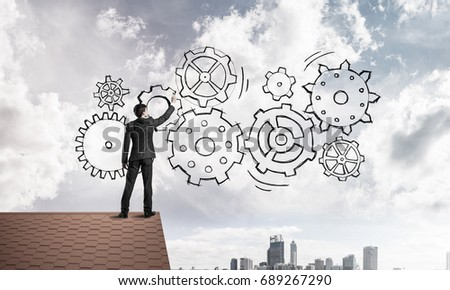 Young businessman standing on house roof and drawing gear mechanism. Mixed media #689267290