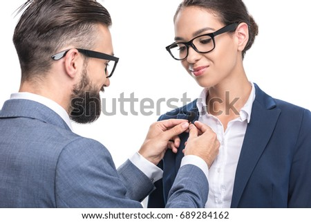 man hanging tie clip microphone on suit of colleague, isolated on white