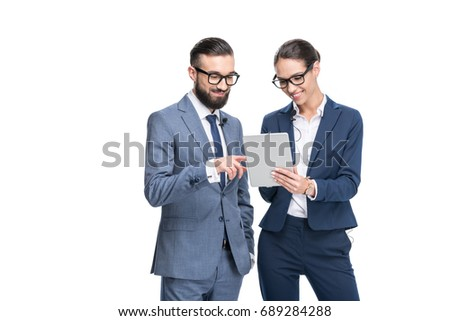 happy businesswoman and businessman in suits using digital tablet, isolated on white