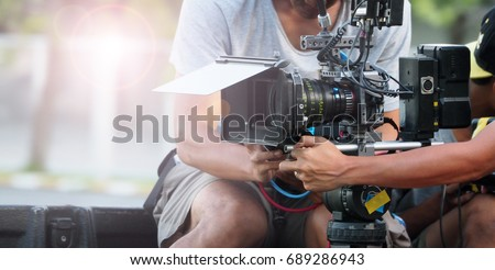 Behind the scenes of movie shooting or video production and film crew team with camera equipment at outdoor location. Royalty-Free Stock Photo #689286943