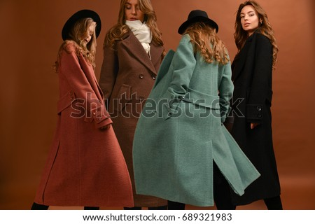 Woman in different colorful long coats, black. brown, dark red, green, with scarf and black hat, with wavy hair on brown background in motion Royalty-Free Stock Photo #689321983