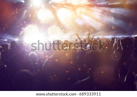 Crowd at concert - Cheering crowd in front of bright colorful stage lights #689333911