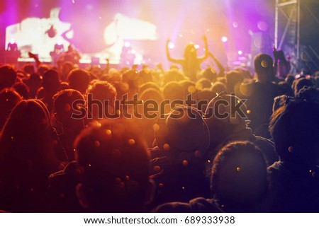 Crowd at concert - Cheering crowd in front of bright colorful stage lights #689333938