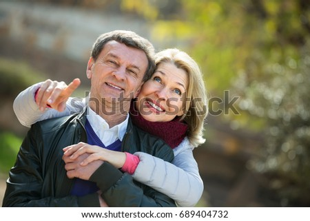 Portrait of smiling mature spouses enjoying spending time at spring park. Focus on woman #689404732