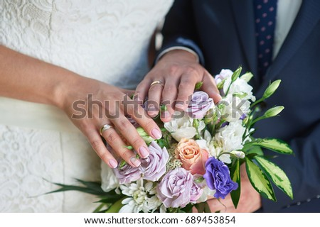 Hands of the bride and groom with rings on a wedding bouquet #689453854