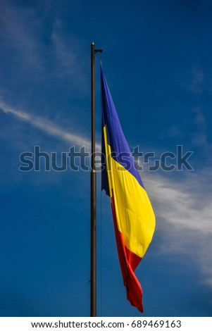 Romanian flag with deep blue sky in the backround. #689469163