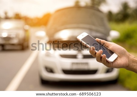 Using a mobile phone call a car mechanic because car was broken. Royalty-Free Stock Photo #689506123