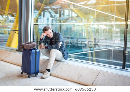 Man upset at the airport his flight is delayed Royalty-Free Stock Photo #689585233