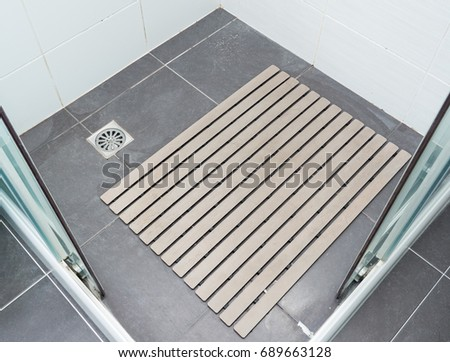 Rubber slip pad with the many hair pieces in the shower stall of the modern house. #689663128