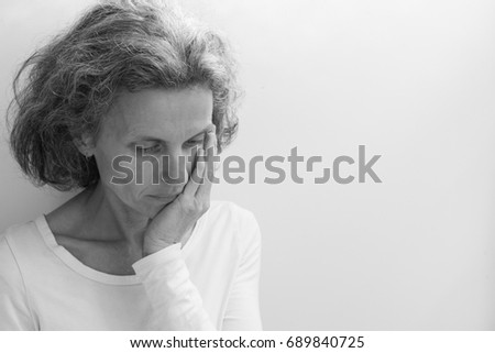Middle aged woman in white top with hand on face against neutral background with copy space to right (black and white, selective focus) Royalty-Free Stock Photo #689840725