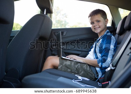 Portrait of teenage boy using laptop in the back seat of car #689945638