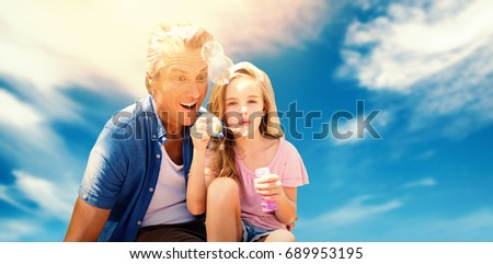 A little girl blowing bubbles with her father against view of a blue sky #689953195