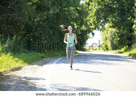Athletic happy brunette woman working out in a meadow, from a complete series of photos #689966026