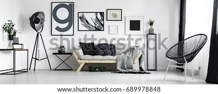 Artist's living room in minimal style with artworks  Royalty-Free Stock Photo #689978848