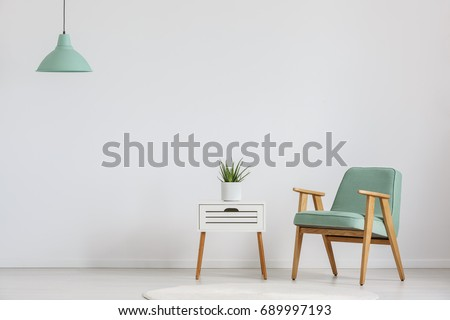 Photo of white wooden cupboard with fresh plant and mint lampshade Royalty-Free Stock Photo #689997193