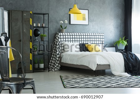 Brass chair in stylish bedroom with white flowers on bolster of king-size bed #690012907