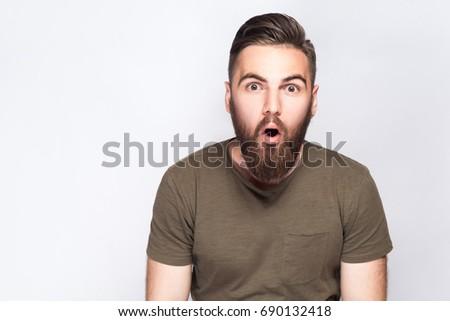 Portrait of surprised bearded man with dark green t shirt against light gray background. studio shot.   #690132418