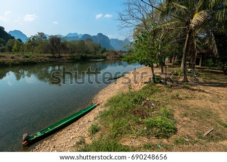 Beautiful landscape picture of the Nam Song River with tropical vegetation and two boats. Close to Tham Chang Cave in the city of Vang Vieng, Laos.