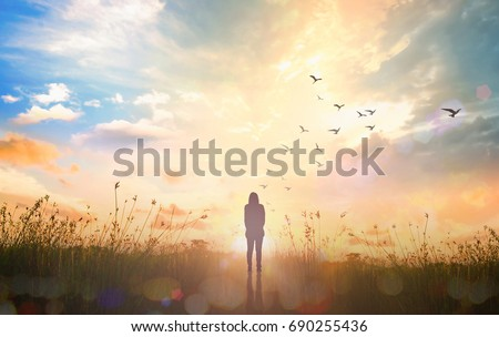 International human rights day concept: Silhouette alone woman standing with birds flying on abstract of heaven background