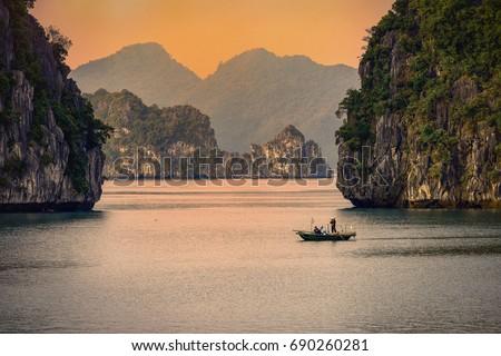 Halong bay boats,Sunset at Ha Long Bay scenic view , Hanoi, Vietnam Royalty-Free Stock Photo #690260281