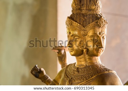 Ayutthaya, Thailand - March, 12, 2017 : Hindu god Brahma gold shabby old statue .Beautiful Indian religion traditional lord sculpture with for faces in Wat Puttaisawan temple, Ayutthaya, Thailand #690313345