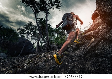 Woman hiker with backpack climbs steep rocky terrain Royalty-Free Stock Photo #690366619