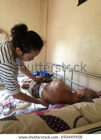 PHANG-NGA, THAILAND - AUGUST 5, 2017: An Asian woman with dark curly hair gently gives a massage to an old skinny Asian man laying bare chest in a bed. #690449908