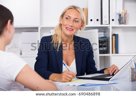 Smiling elegant business woman talking to female colleague in office #690486898