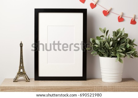 Black frame mock up with Eiffel tower, plant and heart shape garland. Modern stylish interior background for social media and marketing.